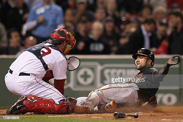 Nick Markakis of the Baltimore Orioles scores a run in the first inning as Jason Varitek of the Boston Red Sox defends in the second game of a...