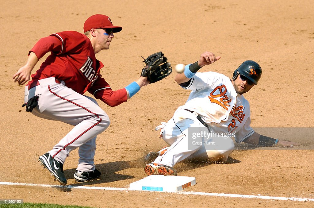 Nick Markakis #21 of the Baltimore Orioles steals third base under the tag of Mark Reynolds #27 of the Arizona Diamondbacks on June 17, 2007 at Camden Yards in Baltimore, Maryland. The Diamondbacks defeated the Orioles 6-4.