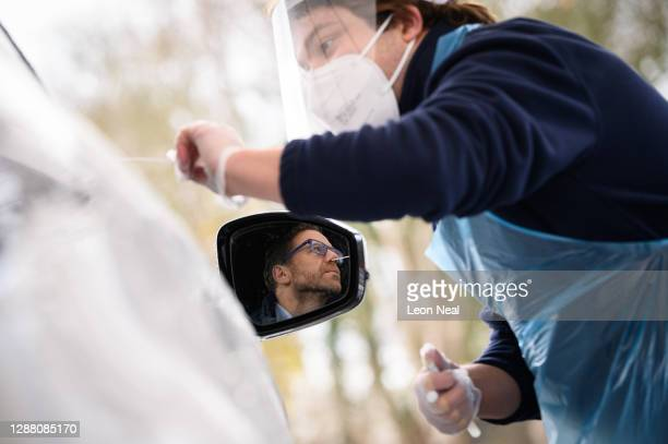 Nick Markham, the founder of ExpressTest, is reflected in his wing mirror as he takes a PCR swab test at Gatwick Airport on November 27, 2020 in...