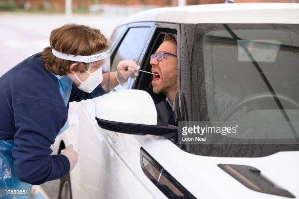 Nick Markham, the founder of ExpressTest, reacts as he takes a PCR swab test at Gatwick Airport on November 27, 2020 in London, England. The airport...