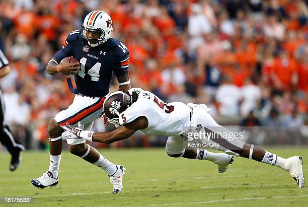 Nick Marshall of the Auburn Tigers breaks a tackle by Jamerson Love of the Mississippi State Bulldogs at JordanHare Stadium on September 14 2013 in...