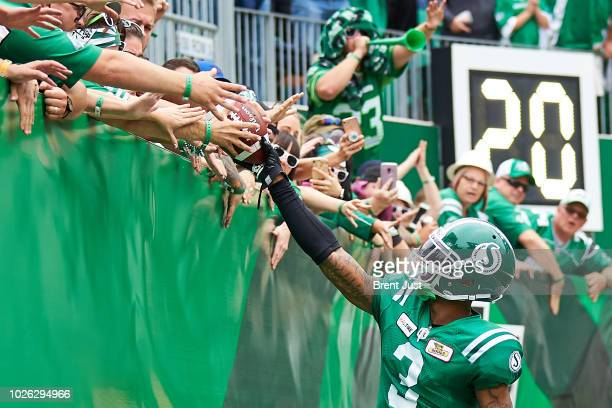 Nick Marshall of the Saskatchewan Roughriders gives the ball to a fan after scoring a late touchdown in the game between the Winnipeg Blue Bombers...