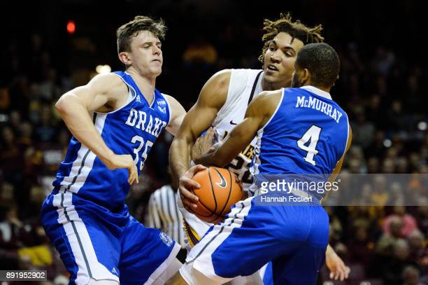 Nick McGlynn and De'Antae McMurray of the Drake Bulldogs defend against Reggie Lynch of the Minnesota Golden Gophers during the game on December 11...