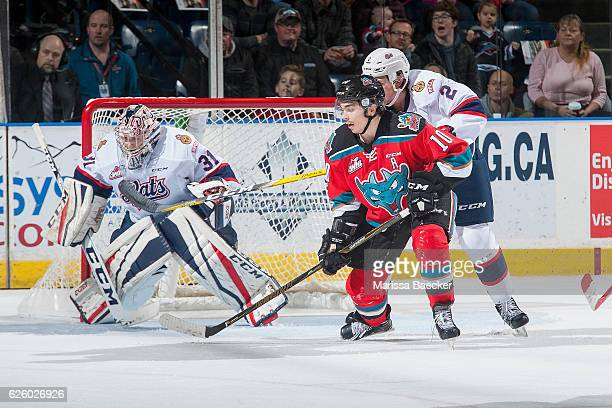 Nick Merkley of the Kelowna Rockets is back checked by Sergey Zborovskiy in front of the net of Tyler Brown of the Regina Pats during first period on...