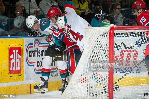 Nick Merkley of the Kelowna Rockets is checked into the boards by a player of the Spokane Chiefs during the third period on March 5, 2014 at Prospera...