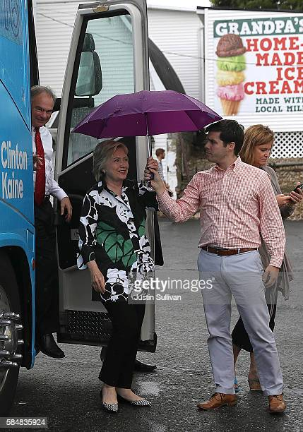 Nick Merrill holds an umbrella for democratic presidential nominee former Secretary of State Hillary Clinton as she walks off of her campaign bus...