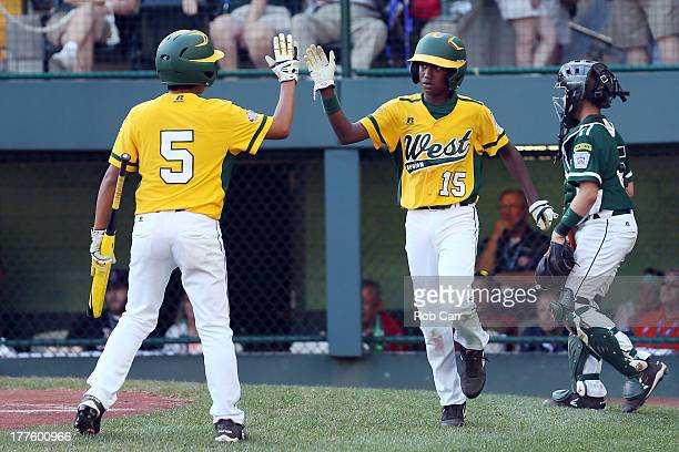 Nick Mora and Michael Gaines of the West team celebrate after Gaines scored on a passed ball during the sixth inning of the West's 121 win over the...