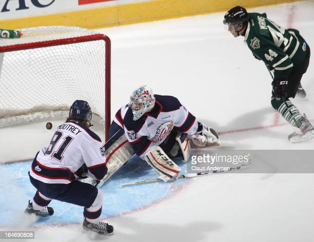 Nick Moutrey and Jake Paterson of the Saginaw Spirit watch a puck go in by Dakota Mermis of the London Knights in a 1st round playoff game on March...