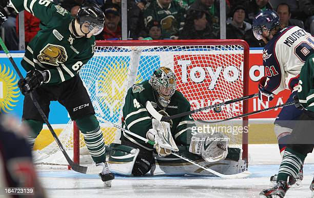 Nick Moutrey of the Saginaw Spirit tries to bat a puck past Anthony Stolarz of the London Knights in a first round playoff game on March 24 2013 at...