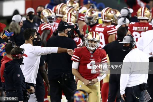 Nick Mullens of the San Francisco 49ers gets a pat on the back from injured starting quarterback Jimmy Garoppolo after throwing a pick six in the...