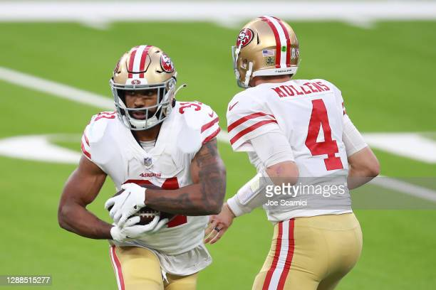 Nick Mullens of the San Francisco 49ers hands off to Raheem Mostert during the second half against the Los Angeles Rams at SoFi Stadium on November...