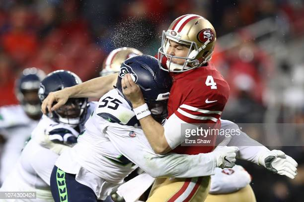 Nick Mullens of the San Francisco 49ers is hit by Frank Clark of the Seattle Seahawks during their NFL game at Levi's Stadium on December 16 2018 in...