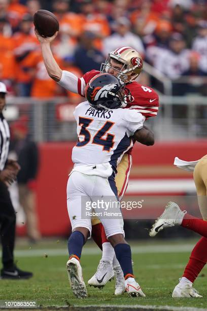 Nick Mullens of the San Francisco 49ers is hit has he throws by Will Parks of the Denver Broncos during their NFL game at Levi's Stadium on December...