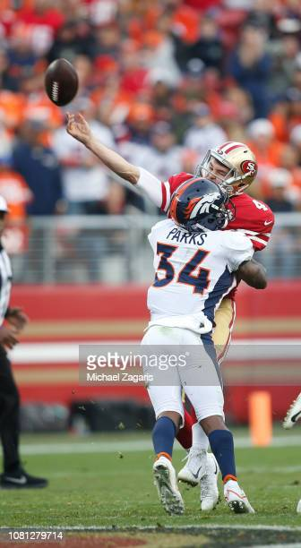 Nick Mullens of the San Francisco 49ers passes has he is hit by Will Parks of the Denver Broncos during the game at Levi's Stadium on December 9 2018...