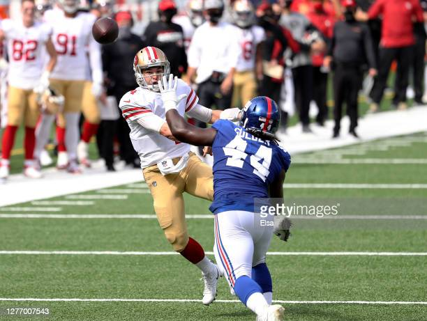 Nick Mullens of the San Francisco 49ers passes under pressure from Markus Golden of the New York Giants in the first quarter at MetLife Stadium on...