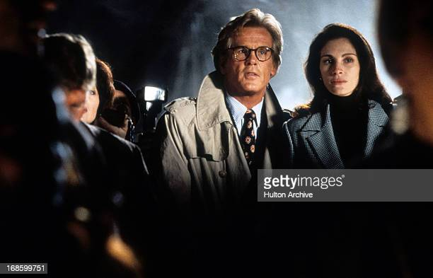 Nick Nolte and Julia Roberts standing next to each other in a scene from the film 'I Love Trouble' 1994