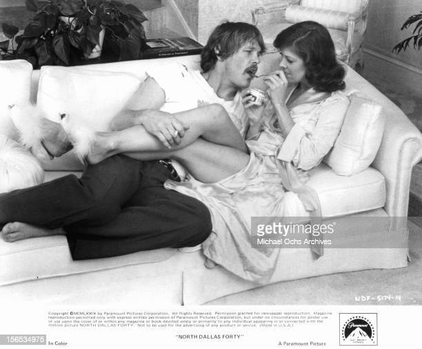 Nick Nolte lies on a couch with Mac Davis in a scene from the film 'North Dallas Forty' 1979