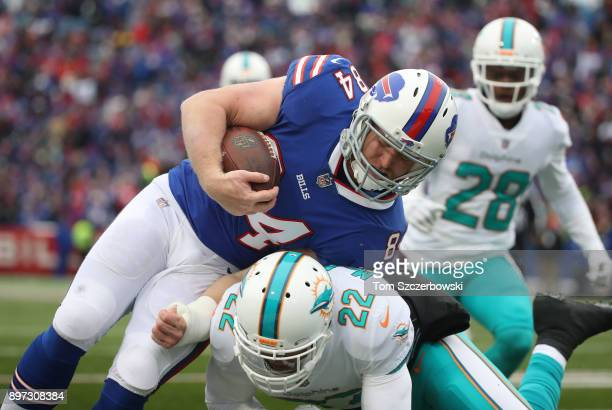 Nick O'Leary of the Buffalo Bills is tackled by TJ McDonald of the Miami Dolphins during NFL game action at New Era Field on December 17 2017 in...
