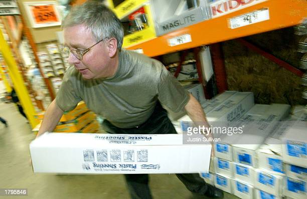 Nick Parham pulls a roll of plastic sheeting from a shelf at Home Depot February 13 2003 in Colma California Americans are stocking up on emergency...