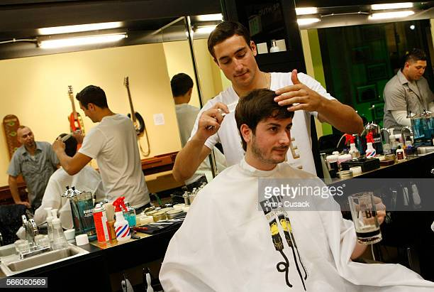Nick Pasqua cuts the hair of Aaron Lippman as he drinks a rootbeer at a new Barber shop in downtown Los Angeles called Bolt and opened by a 46 year...