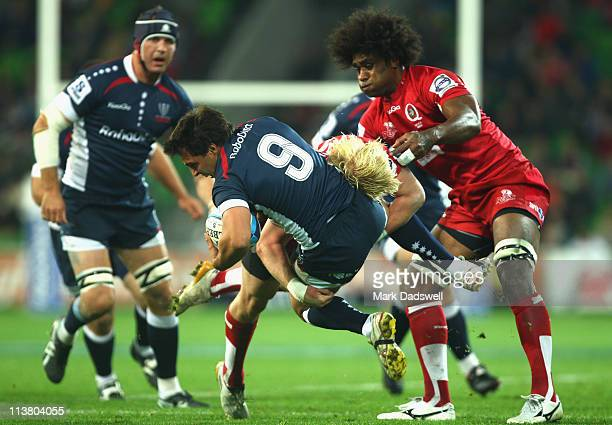 Nick Phipps of the Rebels is driven into the ground by Beau Robinson of the Reds during the round 12 Super Rugby match between the Melbourne Rebels...