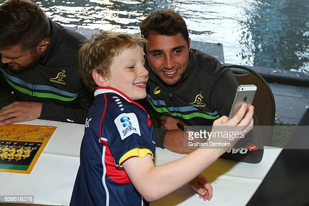 Nick Phipps of the Wallabies poses for a photograph with a young fan during the Australian Wallabies Fan Day at The Crown Promenade River Walk on...