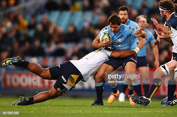 Nick Phipps of the Waratahs is tackled during the round 17 Super Rugby match between the Waratahs and the Brumbies at ANZ Stadium on June 28 2014 in...