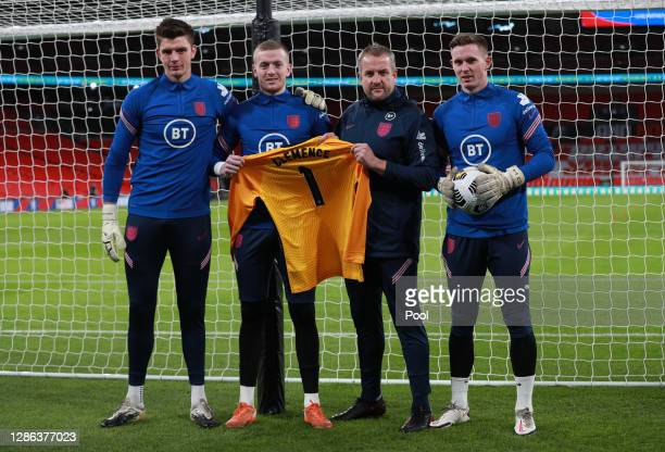 Nick Pope, Jordan Pickford, goalkeeper coach Martyn Margetson and Dean Henderson of England pose for a photo with a tribute shirt in memory of former...
