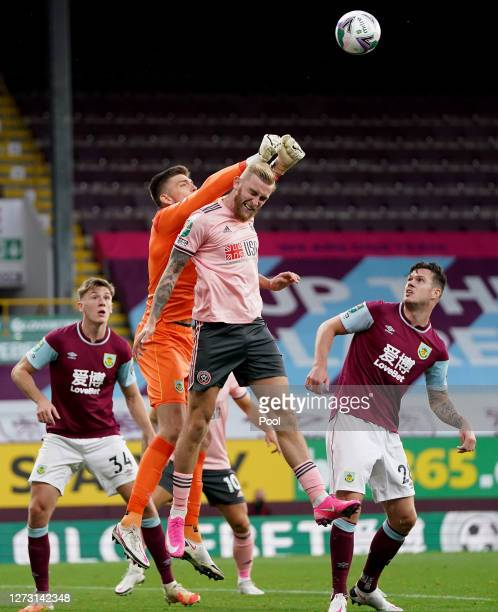 Nick Pope of Burnley punches the ball clear from Oli McBurnie of Sheffield United during the Carabao Cup second round match between Burnley and...