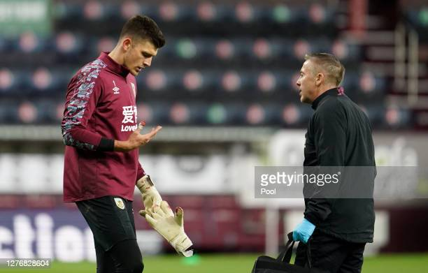 Nick Pope of Burnley receives medical attention for an injury to his thumb during the warm up during the Premier League match between Burnley and...