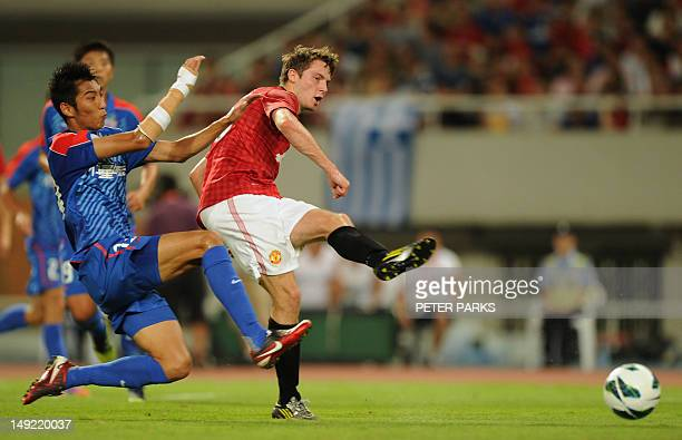Nick Powell of Manchester United kics the ball past Tianyi Qiu of Shanghai Shenhua for a shot on goal during their game at Shanghai Stadium in...