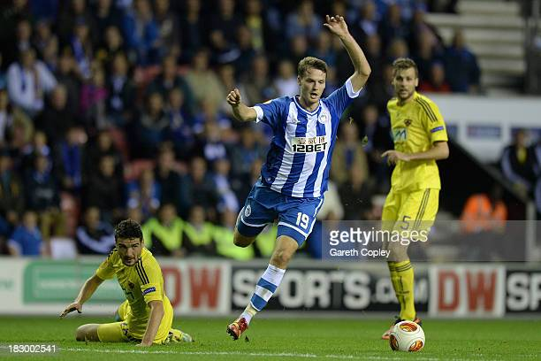 Nick Powell of Wigan gets past Alexsander Rajcevic of NK Maribor on his way to scoring his team's 3rd goal during the UEFA Europa League match...
