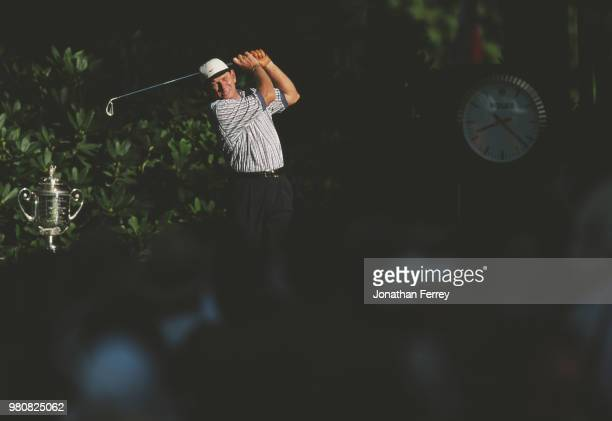 Nick Price of South Africa drives off the tee beside the Professional Golfers' Association trophy during the 80th PGA Championship golf tournament on...