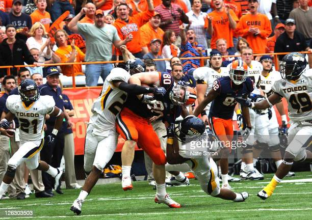 Nick Provo of the Syracuse Orange is tackled by Diauntae Morrow and Jermaine Robinson of the Toledo Rockets during the game on September 24, 2011 at...