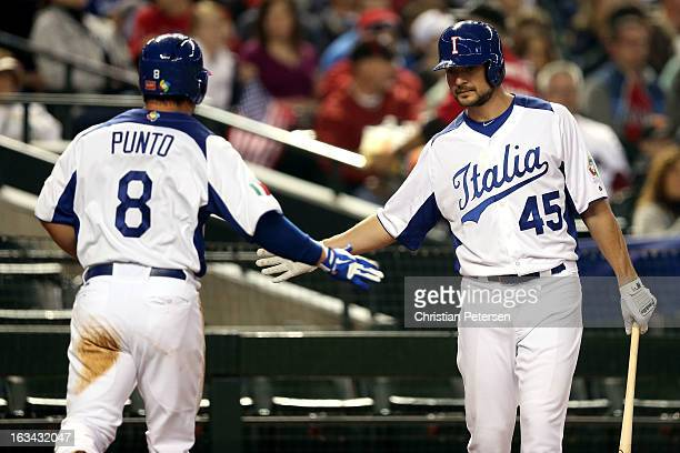 Nick Punto and Mario Chiarini of Team Italy celebrate after scoring a run in the first inning against Ryan Vogelsong of Team USA during the World...