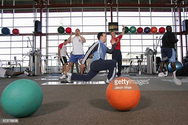 Nick Punto of the Minnesota Twins performs slide board split squats while Texas Rangers Ricky Asadoorian works on slide board lateral squats under...