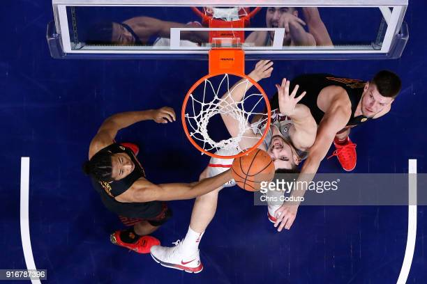 Nick Rakocevic and Elijah Stewart of the USC Trojans fight for a rebound with Dusan Ristic of the Arizona Wildcats during the first half of the...