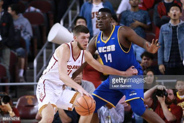 Nick Rakocevic of the USC Trojans handles the ball against Ami Lakoju of the UC Santa Barbara Gauchos during a college basketball game at Galen...