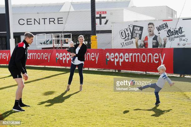 Nick Riewoldt and wife catherine holding son William watch their other son James kick a football after he announces his retirement during a St Kilda...