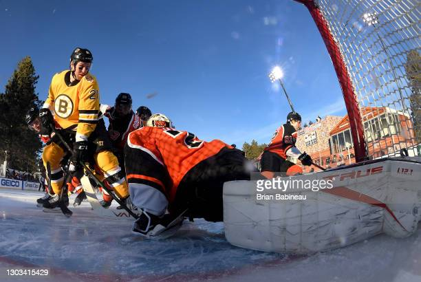 Nick Ritchie of the Boston Bruins challenges goaltender Carter Hart of the Philadelphia Flyers to make a save during the first period of the 2021 NHL...