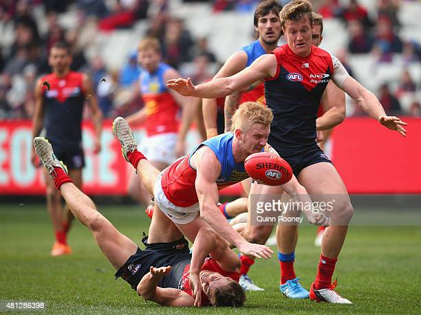 Nick Robertson of the Lions handballs whilst being tackled by Jack Viney of the Demons during the round 16 AFL match between the Melbourne Demons and...
