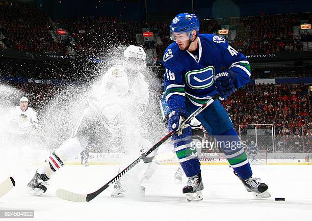 Nick Schmaltz of the Chicago Blackhawks checks Jayson Megna of the Vancouver Canucks during their NHL game at Rogers Arena November 19, 2016 in...