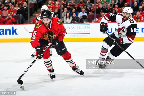 Nick Schmaltz of the Chicago Blackhawks grabs the puck ahead of Jordan Martinook of the Arizona Coyotes in the third period at the United Center on...
