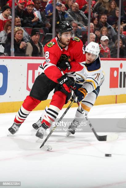 Nick Schmaltz of the Chicago Blackhawks hits the puck past Evan Rodrigues of the Buffalo Sabres in overtime at the United Center on December 8 2017...