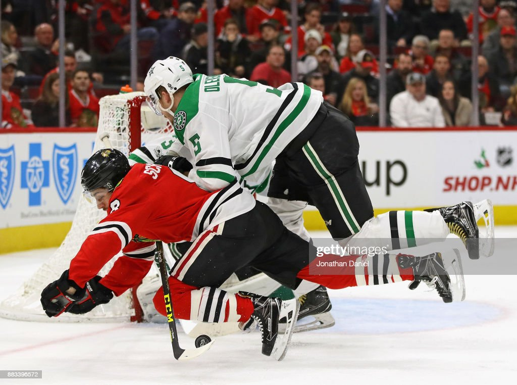Nick Schmaltz #8 of the Chicago Blackhawks is shoved to the ice by Jamie Oleksiak #5 of the Dallas Stars at the United Center on November 30, 2017 in Chicago, Illinois. The Stars defeated the Blackhawks 4-3 in overtime.