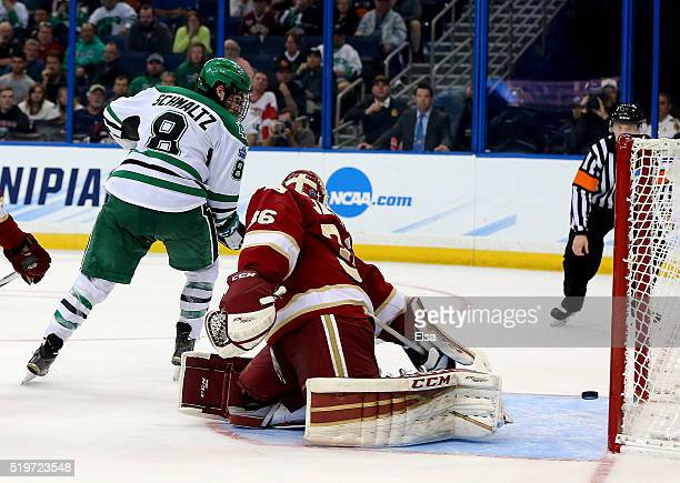 Nick Schmaltz of the North Dakota Fighting Hawks scores the game winning goal in the third period as Tanner Jaillet of the Denver Pioneers defends...