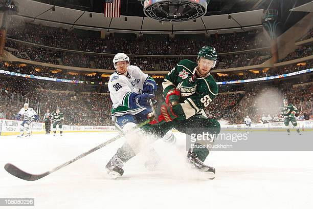 Nick Schultz of the Minnesota Wild and Jannik Hansen of the Vancouver Canucks skate to the puck during the game at Xcel Energy Center on January 16,...