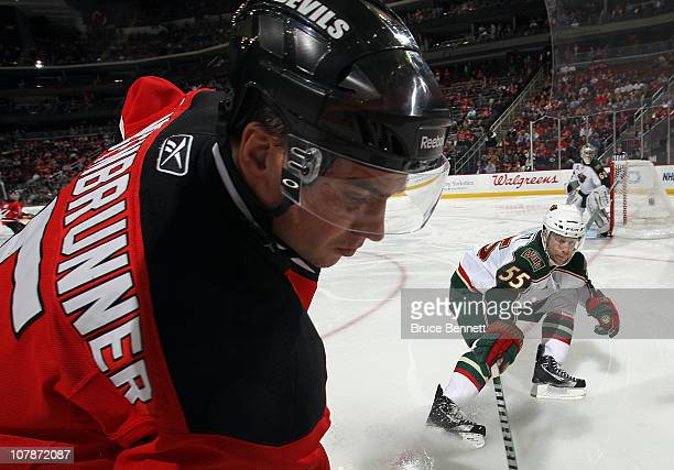 Nick Schultz of the Minnesota Wild checks Jamie Langenbrunner of the New Jersey Devils at the Prudential Center on January 4, 2011 in Newark, New...