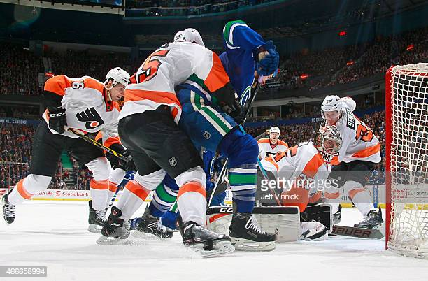 Nick Schultz of the Philadelphia Flyers grabs Shawn Matthias of the Vancouver Canucks beside Steve Mason of the Flyers during their NHL game at...