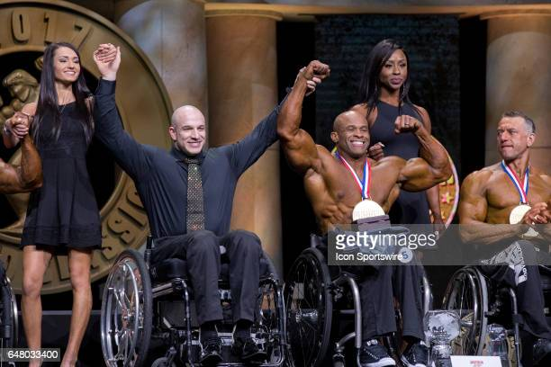Nick Scott hold up the hand of Harold Kelley after kelly won his second Pro Wheelchair as part of the Arnold Sports Festival on March 4 at the...